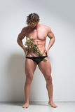 Athletic man with a withered flowers Royalty Free Stock Photos