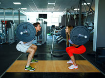 Athletic man and woman with barbell doing squats in the gym Royalty Free Stock Images