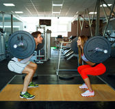 Athletic man and woman with barbell doing squats in the gym Royalty Free Stock Photos