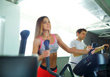 Athletic man and woman doing cardio training program in fitness. Athletic couple - men and women doing cardio training program in fitness center Stock Photo