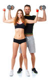 Athletic man and woman with dumbbells on the white. Athletic men and women with dumbbells on the white background royalty free stock images