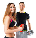 Athletic man and woman with dumbbells on the white. Athletic men and women with dumbbells on the white background stock photo