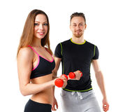 Athletic man and woman with dumbbells on the white. Athletic men and women with dumbbells on the white background stock images