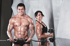 Athletic man and woman with a dumbells. Stock Photography