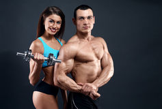 Athletic man and woman with a dumbells Royalty Free Stock Photography