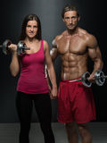 Athletic Man And Woman With A Dumbells Stock Images