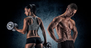 Athletic man and woman with a dumbells. Stock Image