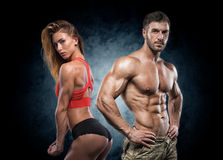 Athletic man and woman. Fitness couple. Man and women on a dark background. Fitness couple stock photography