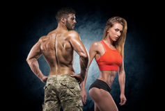 Athletic man and woman. Fitness couple. Man and women on a dark background. Fitness couple royalty free stock photos