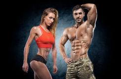 Athletic man and woman. Fitness couple. Man and women on a dark background. Fitness couple royalty free stock photo