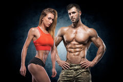 Athletic man and woman. Fitness couple. Man and women on a dark background. Fitness couple royalty free stock image
