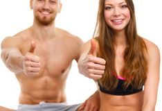 Athletic man and woman after fitness exercise with a finger up o. Athletic men and women after fitness exercise with a finger up on the white background stock photos