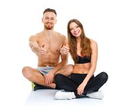 Athletic man and woman after fitness exercise with a finger up o. Athletic men and women after fitness exercise with a finger up on the white background stock photography