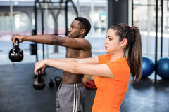 Athletic man and woman working out. Athletic men and women working out at crossfit gym Stock Image