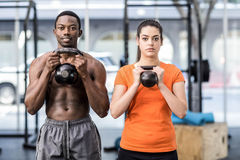 Athletic man and woman working out. Athletic men and women working out at crossfit gym Royalty Free Stock Photo