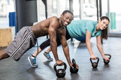Athletic man and woman working out. Athletic men and women working out at crossfit gym Stock Photo