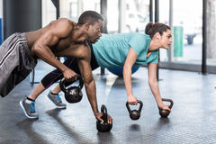 Athletic man and woman working out. Athletic men and women working out at crossfit gym Royalty Free Stock Images