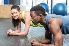 Athletic man and woman working out. Athletic men and women working out at crossfit gym Royalty Free Stock Image