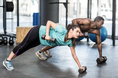 Athletic man and woman working out. Athletic men and women working out at crossfit gym Stock Photos