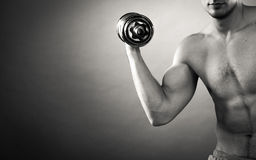 Athletic man working with heavy dumbbells Royalty Free Stock Photography
