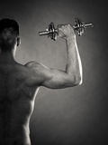 Athletic man working with heavy dumbbells Stock Image