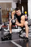 Athletic man working with heavy dumbbells at the gym Royalty Free Stock Photos