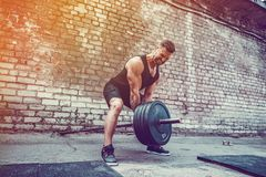 Athletic man working out with a barbell. Strength and motivation. Exercise for the muscles of the back. Athletic man working out with a barbell in front of brick stock photography