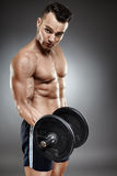 Athletic man working out with dumbbells Royalty Free Stock Images