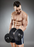 Athletic man working out with dumbbells Stock Photo