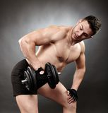 Athletic man working out with heavy dumbbells Stock Image