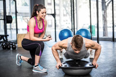 Athletic man working out helped by trainer woman Stock Image