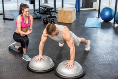 Athletic man working out helped by trainer woman Stock Images