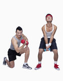 athletic man and workout beginner struggling,  opposite, studio shot Royalty Free Stock Image