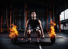 Athletic man works out at the gym with a fiery barbell. Determined athletic man works out at the gym with a fiery barbell stock photo