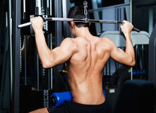 Athletic man works out on simulator Stock Photos