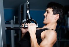 Athletic man works out on training apparatus stock images