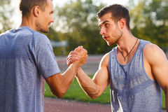 Athletic men in workout clothes handshake on summer hot day. Two athletic men in workout clothes shake hands on summer hot day Stock Images