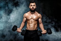 Athletic muscular man doing exercises with dumbbells. stock photo