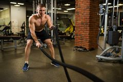Athletic muscular man engaged with a thick rope with a bare torso in the gym. Photo royalty free stock photography