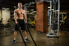 Athletic muscular man engaged with a thick rope with a bare torso in the gym. Photo stock images
