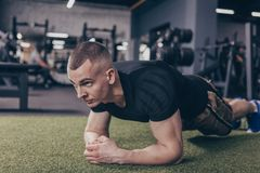 Athletic muscular man exercising at the gym stock image