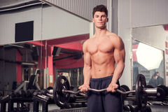 Athletic muscular man in gym exercising Stock Photo