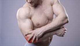 Athletic muscular man has pain in the elbow. Red spot of injury Royalty Free Stock Photography