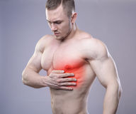 Athletic muscular man has pain in the heart. Red Royalty Free Stock Images