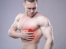 Athletic muscular man has pain in the heart. Red spot of injury Royalty Free Stock Image