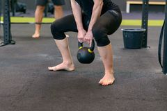 Athletic muscular woman lifting kettle weights. Athletic muscular women lifting kettle weights in a gym as she does a training workout in a health and fitness royalty free stock image