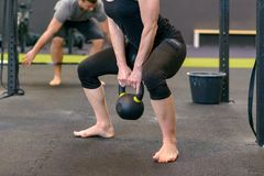 Athletic muscular woman lifting kettle weights. Athletic muscular women lifting kettle weights in a gym as she does a training workout in a health and fitness royalty free stock photos