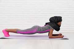 Athletic muslim woman doing exercise plank on yoga mat. stock photos