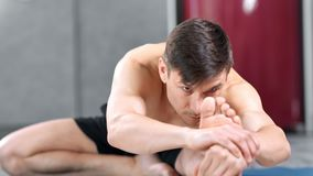 Athletic naked male making stretching reaching for bare foot medium close-up. Flexible focused Caucasian man practicing yoga pilates enjoying healthy lifestyle stock video