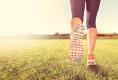 An athletic pair of legs on grass during sunrise or sunset Royalty Free Stock Image